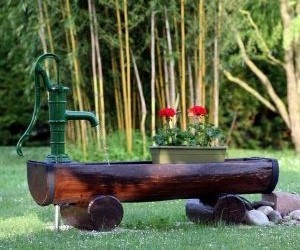 Brunnen aus halbem Holzstamm im Garten