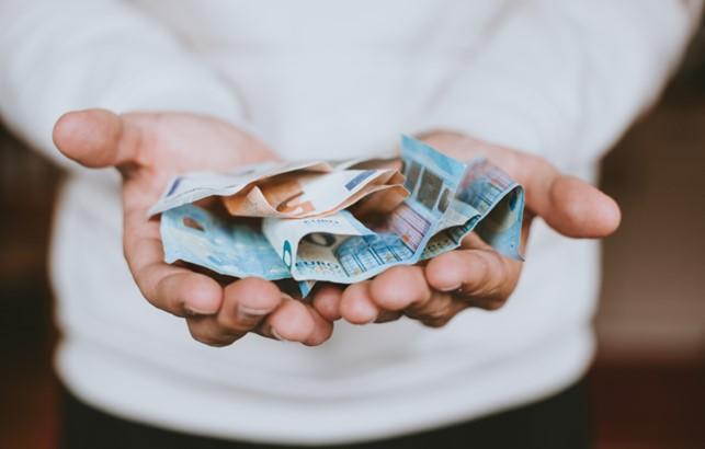 Mann hält Geldscheine in den Händen