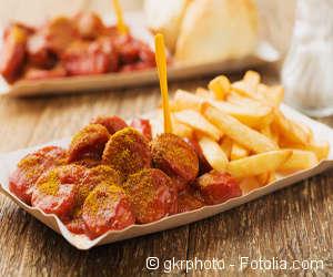 Currywurst mit Pommes in einer Pappschale.