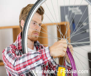 Junger Mann repariert einen Fahrradreifen in einer Garage.