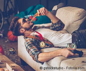 Ein junger Mann liegt entspannt auf dem Sofa und beißt genüsslich in ein Stück Pizza. Um ihn herum Chaos und Dreck.