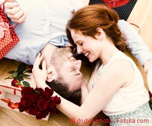 Frau beißt Mann unter Herzchen-Decke verliebt in die Nase