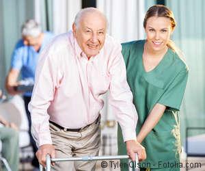 Pflegekraft hilft einem alten Herren