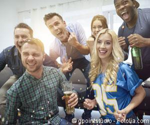 Männer und Frauen jubeln vor dem Fernseher mit Bier in der Hand