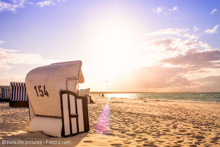 Ein Strandkorb von hinten abgebildet steht auf dem Strand mit Blick auf das Meer.